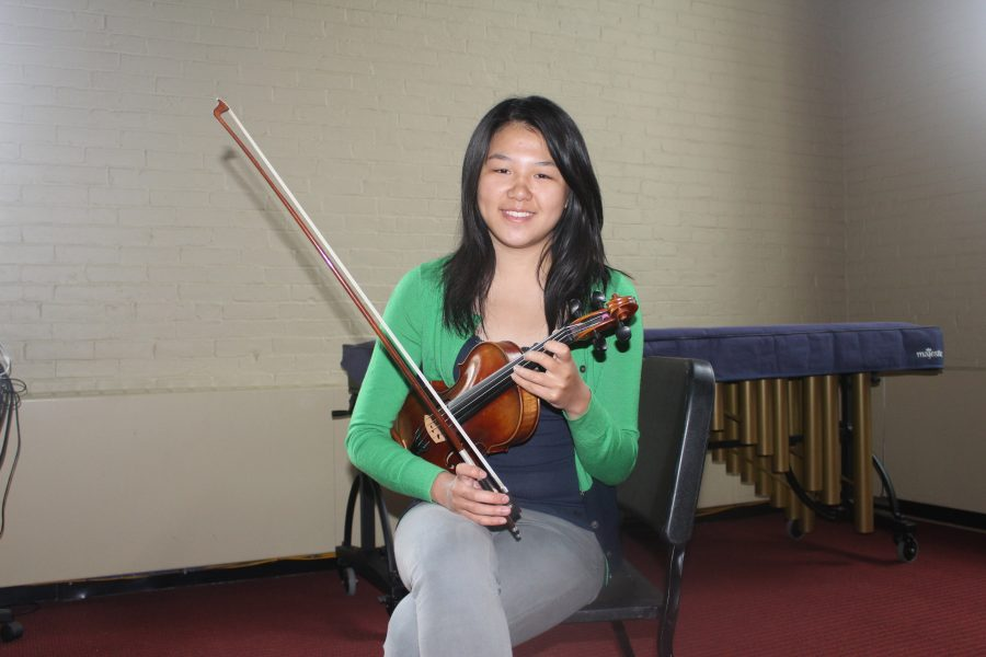 Candace practices her violin in the orchestra.