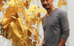 Fred Liang posing in front of one of his golden paper and light pieces.