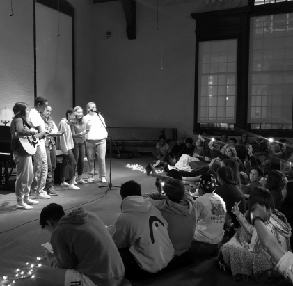 Students performing at the first Open Mic of this academic year, the audience showing their support by waving phone flashlights in time to the song.