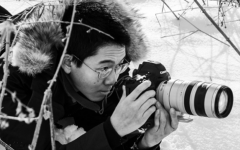 Teddy Deng '20 crouching in the snow to get the perfect shot.